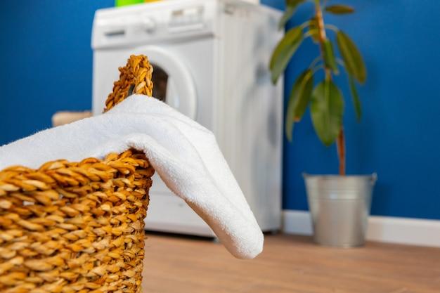 Machine à laver avec du linge sur le mur bleu