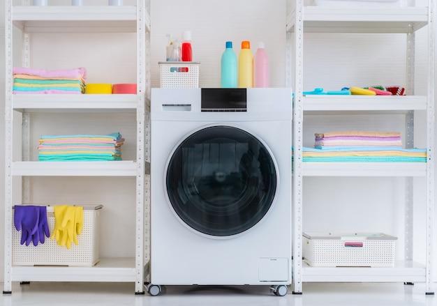 Machine luandry blanche avec du liquide de lavage en poudre et des équipements sur une étagère latérale avec des vêtements propres et colorés.