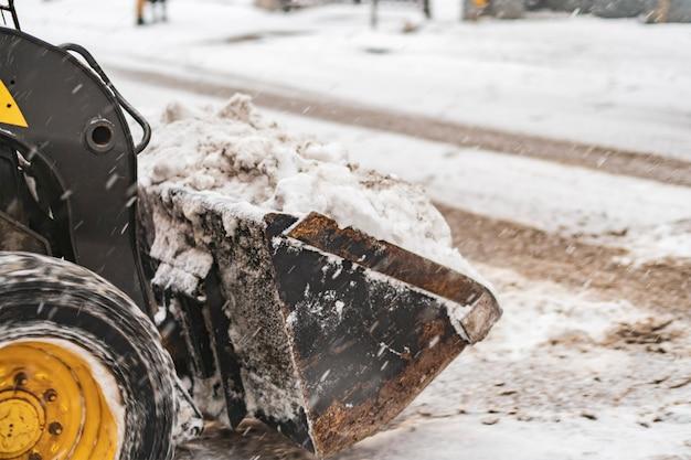 La machine à nettoyer la neige travaille dur dans les rues de la ville b