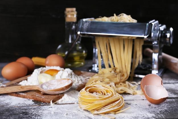 Machine à pâtes en métal et ingrédients pour pâtes sur bois
