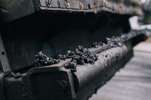 Machine de pavage déposant de l'asphalte ou du bitume frais sur la base de gravier lors de la construction d'une autoroute. nouvelle route
