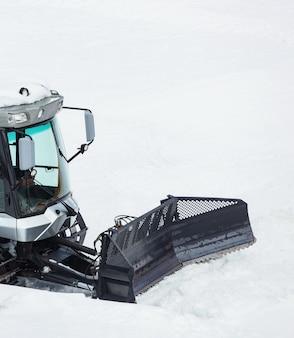 Machine de piste, neige cat. motoneige régissant la route de montagne enneigée.