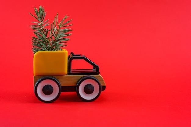 La machine porte des arbres de noël sur fond rouge avec un espace de lance.
