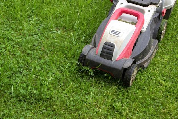 Machine pour couper les pelouses. fond de jardinage. équipement d'outils électriques de jardin.