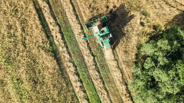 Machine de récolte travaillant dans le champ vue aérienne d'en haut, moissonneuse-batteuse machine agricole récolte champ de blé mûr