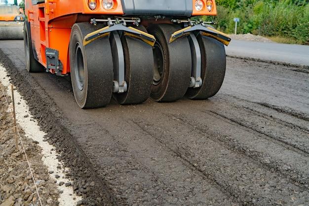 La machine à rouleaux fonctionne sur l'asphalte.