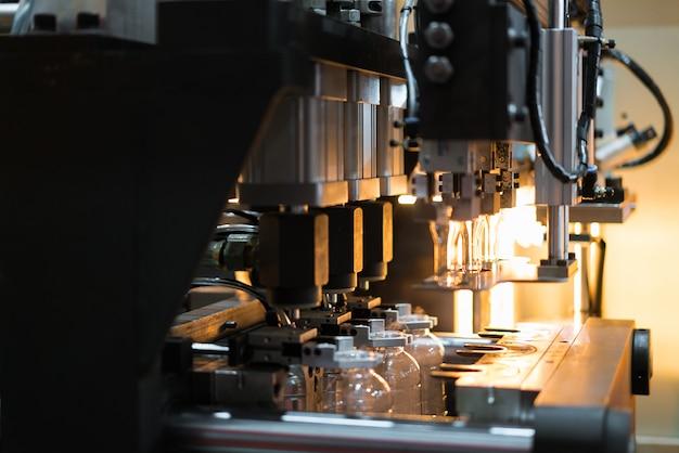 Machine de soufflage de bouteilles pet / plastique automatique travaillant en usine.