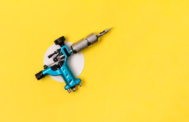 Machine à tatouer bleue sur jaune. disposition minimale du studio d'artiste tatoueur