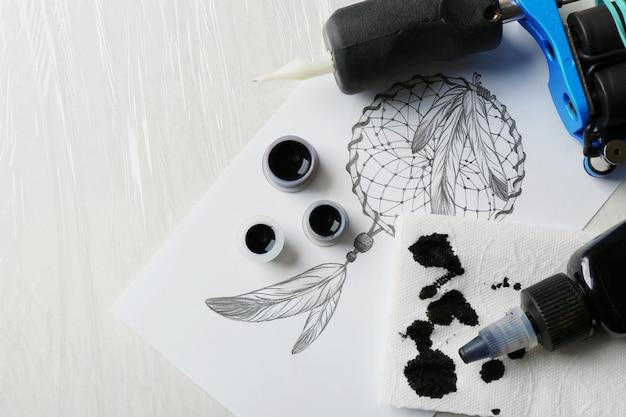 Machine à tatouer, croquis et fournitures sur table