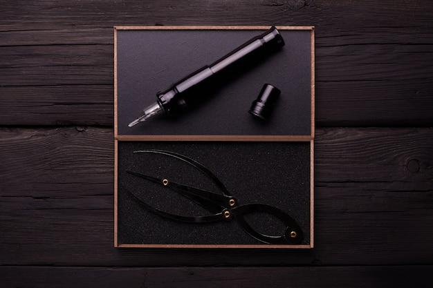 Machine à tatouer sur un fond en bois noir. tubes, pointes, poignées pour le tatouage.