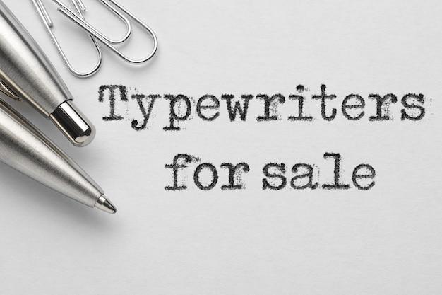 Machines à écrire à vendre mots tapés près d'un stylo à bille en métal et des trombones