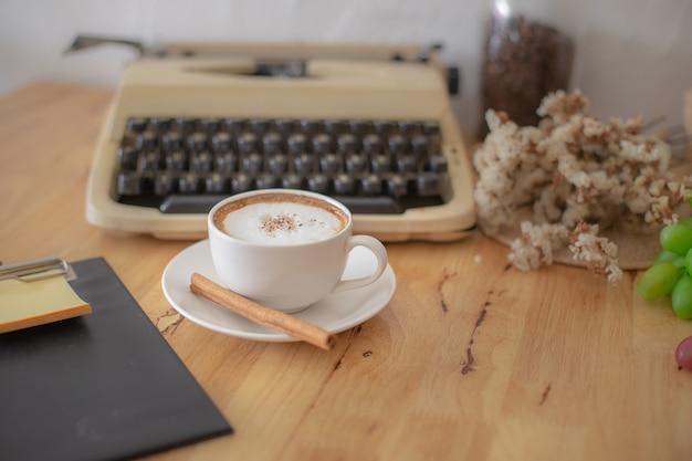 Machines à écrire vintage et tasse de café sur une table en bois.