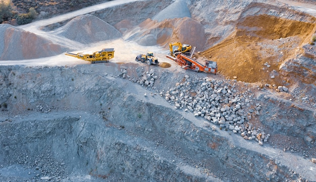 Machines d'excavatrice, de bulldozer et de convoyeur au-dessus de la carrière de pierre, vue aérienne