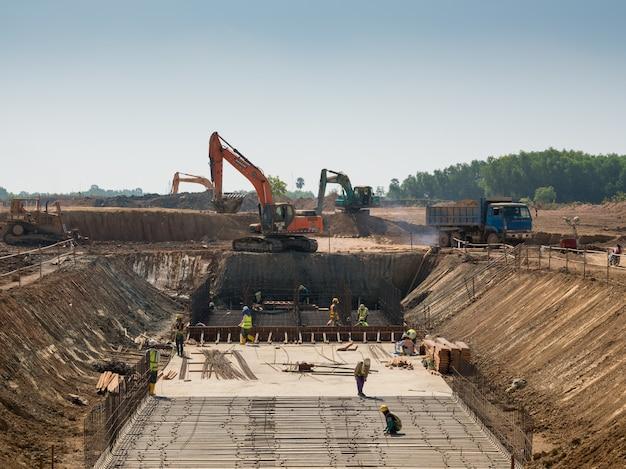 Machines lourdes et travailleurs de la construction travaillant sur un bâtiment