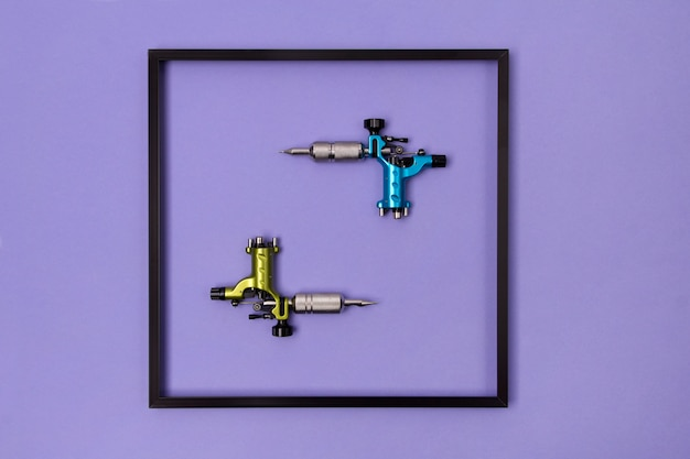 Machines à tatouer dans un cadre violet. maquette pour studio d'artiste de tatouage