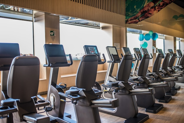 Machines à vélo dans une salle de sport avec une belle lumière du tapis roulant de fenêtre