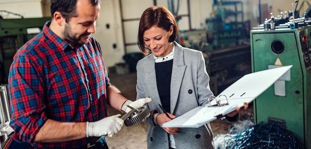 Machiniste debout avec une ingénieure et mesure le diamètre de la roue dentée