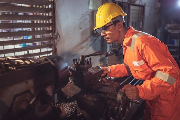Machiniste professionnel: un ouvrier manipule du métal sur la machine de meulage de tour en uniforme avec sécurité