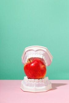 Les mâchoires en plastique tiennent la pomme rouge dans les dents concept de santé dentaire et de dentisterie art créatif coloré