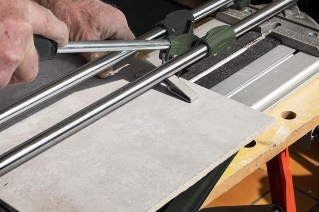 Le maçon coupe un carreau de céramique avec un coupe-carreaux