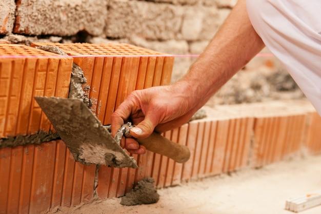 Maçon faisant le mur avec la brique et le coulis