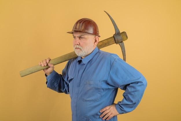 Maçon mâle dans un casque avec pioche travailleur de la construction détient pioche homme entrepreneur avec hache