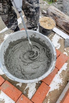 Un maçon mâle mélange le mortier pour la maçonnerie d'un mur de briques