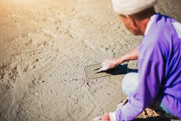 Maçon nivelant le béton à la truelle, les mains écartant le béton coulé.