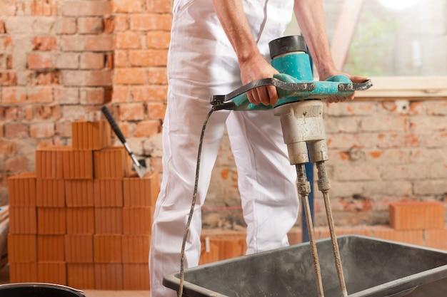 Maçon avec outil mécanique sur chantier