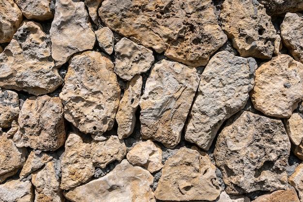 Maçonnerie en calcaire - le mur est en pierre sauvage. la surface est décorée avec un matériau naturel.