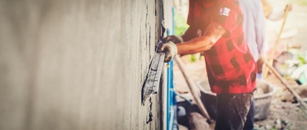 Maçonnerie rurale thaïlandaise plâtrage de béton pour construire travailleur de fond de mur industriel