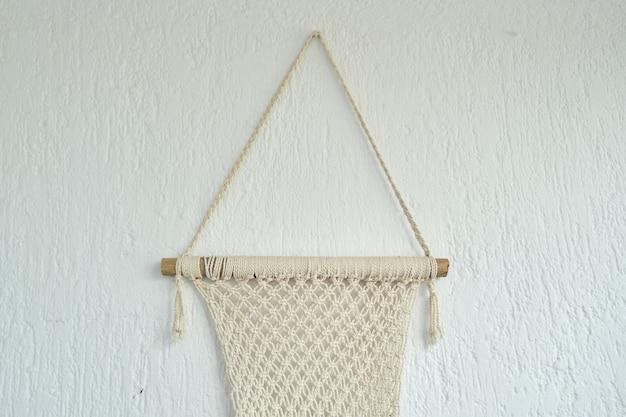 Macramé fait à la main, panneau décoratif tissé à partir de cordes de coton léger sur le mur.