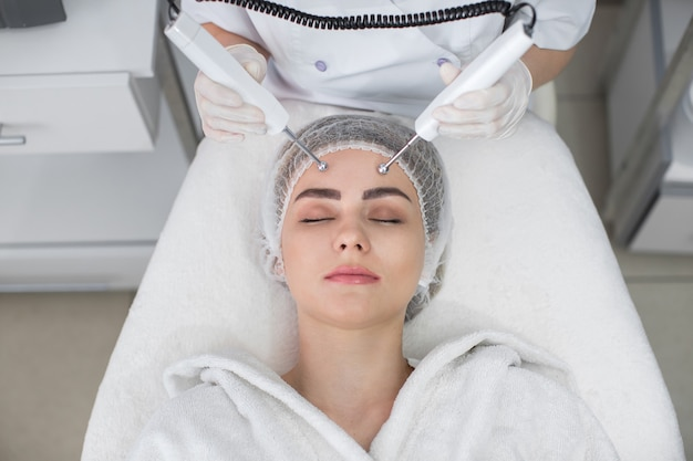 Macro close up portrait de femme ayant un traitement de beauté galvanique cosmétique dans le spa. thérapeute appliquant un courant basse fréquence avec des électrodes sur le visage