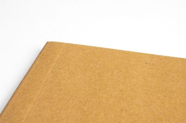 Macro de coin de cahier vierge avec couverture rigide en carton isolé sur blanc
