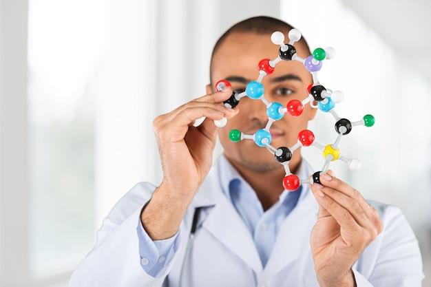 Macro d'un étudiant dans un laboratoire de chimie tenant dans les mains et analysant le modèle moléculaire dmt