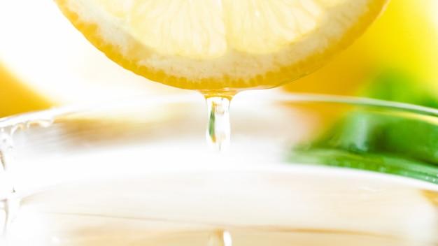 Macro de gouttelette de miel tombant d'une tranche de citron coupée.