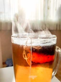 Macro image de vapeur s'écoulant du thé chaud dans une tasse en verre contre la lumière du soleil