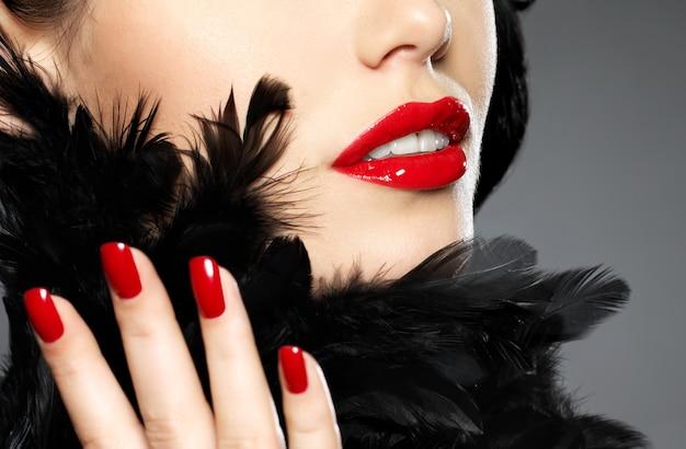 Macro photo de femme avec des ongles rouges fashion et des lèvres sensuelles
