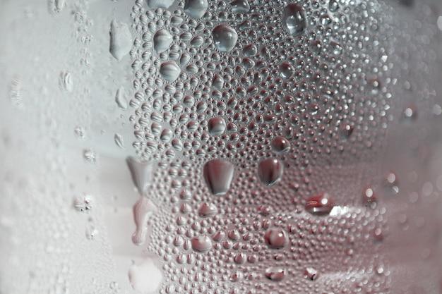 Macro photo de goutte d'eau texturé sur fond de bouteille d'eau potable.