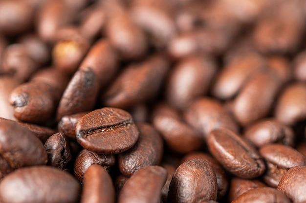 Une macro photo de grains de café bruns frits sur la table. fond de café
