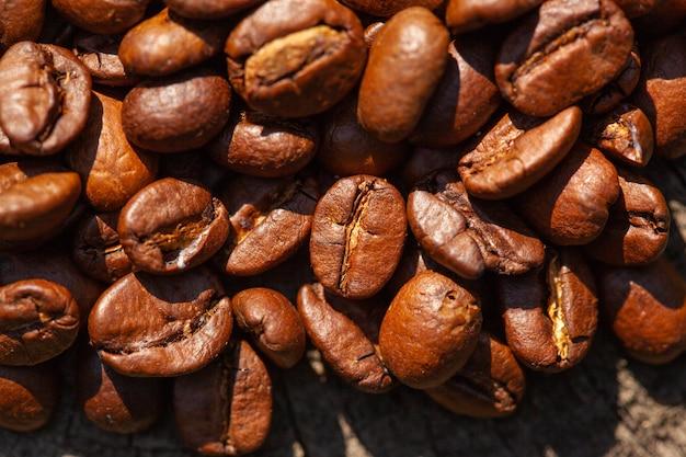 Macro photo des grains de café torréfiés, peut être utilisée comme arrière-plan