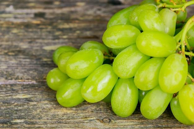 Macro de raisins blancs. des raisins avec des gouttes d'eau. raisins et liège. raisins sur fond en bois