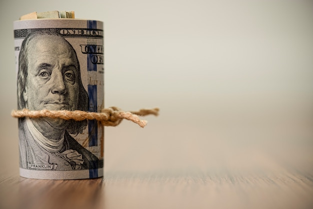 Macro de rouleau de billet de 100 dollars américains sur fond en bois et espace de copie
