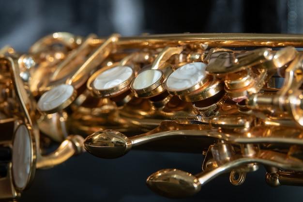 Macro de saxophone ténor doré avec mise au point sélective sur fond noir