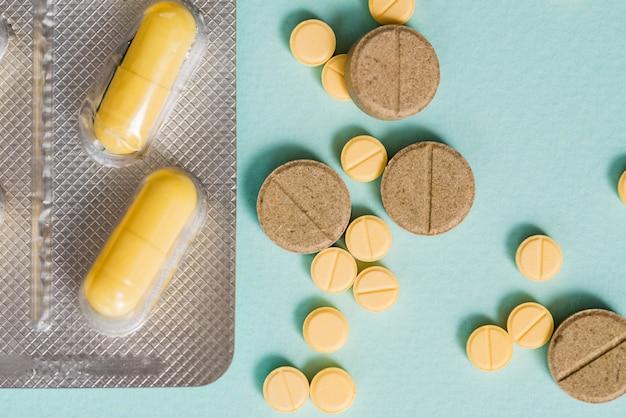 Macro shot détail de comprimés comprimés ovales jaunes avec blister sur fond blanc avec espace de copie