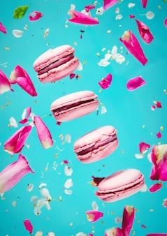 Macrons roses et pétales de rose volent dans l'air sur un mur bleu