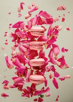 Des macrons roses et des pétales de rose volent dans l'air sur une surface grise