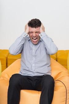 Mad jeune homme assis sur le pouf au bureau en pleurant