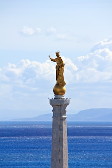 La madonna della lettera est une statue dorée de 20 pieds de haut sur un haut piédestal qui veille sur le port principal de messine sur l'île de sicile en italie