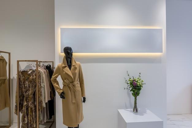 Magasin de vêtements dans un style moderne avec des vitraux en verre et des vêtements sur un cintre